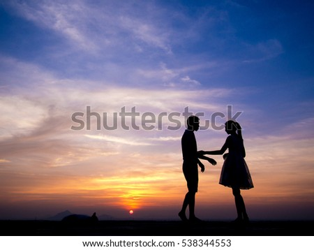Silhouettes of couple man and woman talking in sunset,sweet moment in relationship
