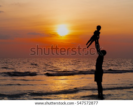 silhouettes of father and son play at sunset beach. Happy family concept