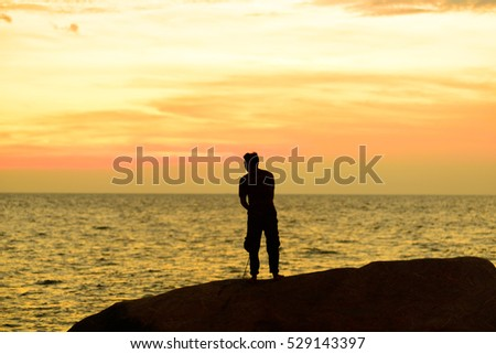 Silhouettes of Fisherman on the beach at sunset