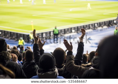 Silhouettes of hands and the fans in the stadium