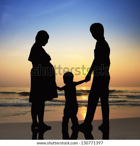 Silhouettes of Happy family the concept of parents and son with beach at sunset