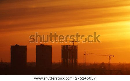 Silhouettes of houses under construction against the sunset