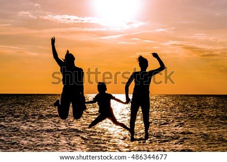 Silhouettes of mother and kids jumping on beach at sunset