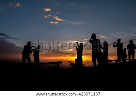 Silhouettes of people enjoying a beautiful sunrise on top of mountain with sunrise at samer dao mountain, Nan province, Thailand