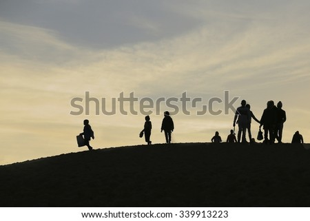 Silhouettes of people walking home after watching the sunset