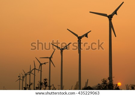 Silhouettes of wind turbines in a sunset