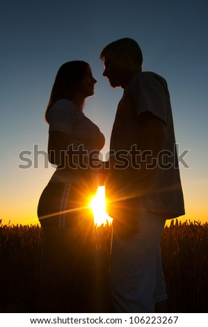 Silhouettes of young couple at sunset on beautiful summer day.