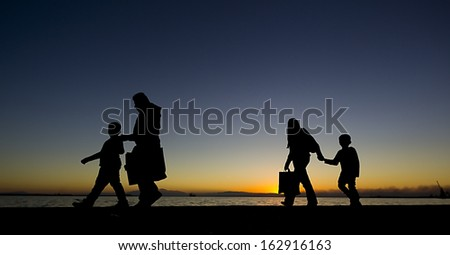 Silouetes of people walking on the sunset
