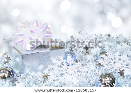 Silver Christmas scene with gift box, baubles and abstract light background