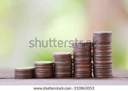 silver coin stack in business growth concept on wood floor with colorful nature background.