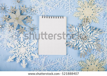 Silver decorative snowflakes and a notebook on a blue wooden background. Christmas decorations closeup.