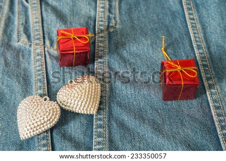 Silver heart gift box on jeans for background.
