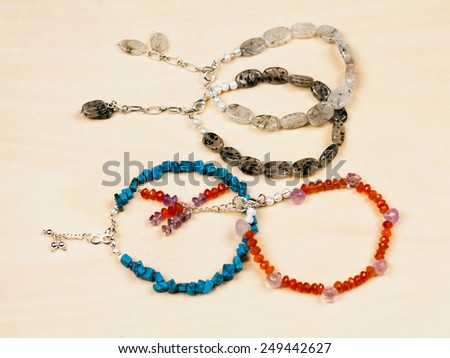 Silver jewels with colorful precious stones and light grey background