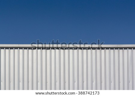 silver metal sheets panel and roof of factory against blue sky