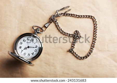 Silver pocket clock on old paper background