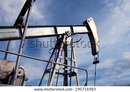 silver pump jack in crude oil field mine