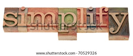 simplify- word in vintage wooden letterpress printing blocks, stained by color inks, isolated on white