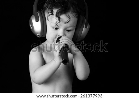 Sing baby with headphone and microphones, on a black background.