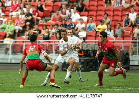 SINGAPORE-APRIL 16: England 7s Team (white) plays against Portugal 7s team (red/green) during Day 1 of HSBC World Rugby Singapore Sevens on April 16, 2016 at National Stadium in Singapore