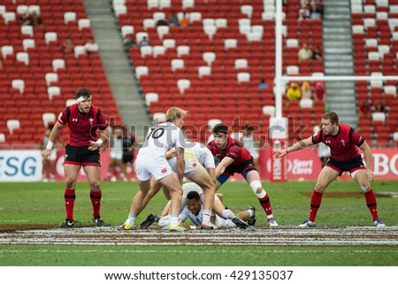 SINGAPORE-APRIL 17: England 7s Team (white) plays against Wales 7s team (red) during Day 2 of HSBC World Rugby Singapore Sevens on April 17, 2016 at National Stadium in Singapore