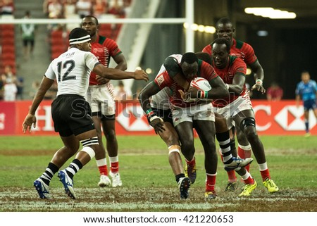 SINGAPORE-APRIL 17:Kenya 7s Team (red) plays against Fiji 7s team (white) during cup final match on Day 2 of HSBC World Rugby Singapore Sevens on April 17, 2016 at National Stadium in Singapore