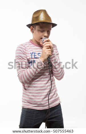 singer brunette boy in a pink jersey in gold hat with a microphone on a white background