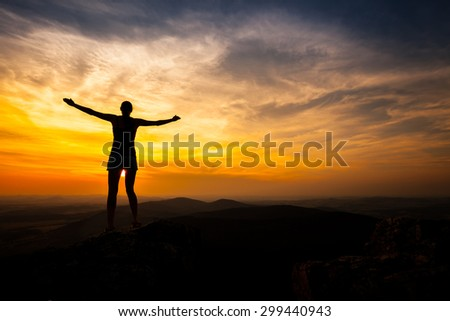 single adult woman silhouette on rock relaxing in sunset