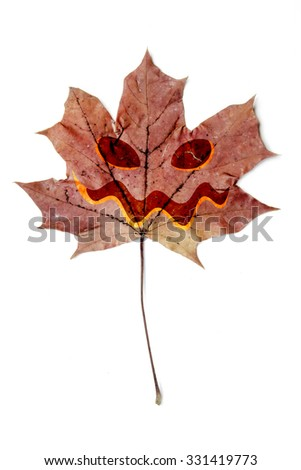 Single autumn leaf with halloween face, isolated