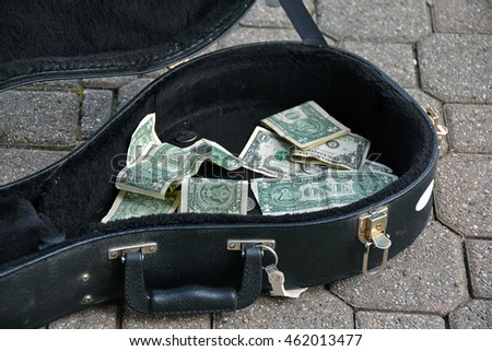 single dollar bills from tips in black guitar case