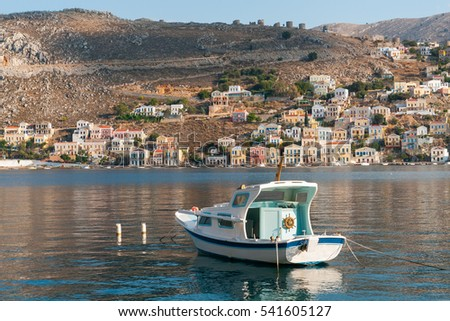 single motorboat and small colored stone house located on the slopes of the mountains in the bay on the coast of the Aegean Sea, Ano Symi city, Simi - one of Dodecanese island, Greece