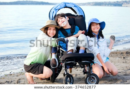 Sisters taking care of disabled brother in wheelchair on beach