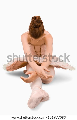 Sitting ballerina doing stretches against a white background