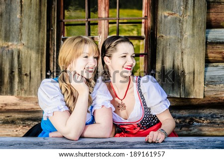Sitting Woman in traditional austrian clothes in front of a wooden hut