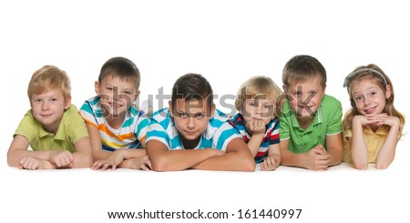 Six children are lying on the floor on a white background
