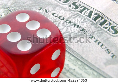 Six sided red die on dollar banknote; Symbol of fortune; Macro photo