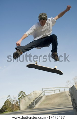 Skate boarder jumping with board flipping