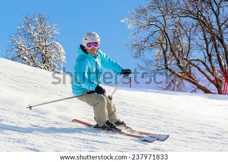 Skier at high speed on piste in soft snow on a sunny day on a background of trees and cloudless blue sky. Shallow depth of field