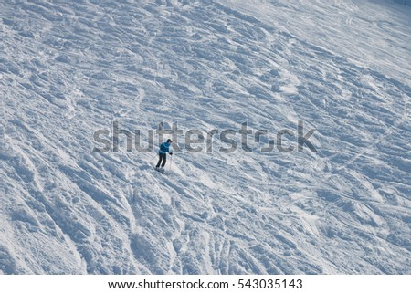 Skier in a blue jacket and helmet rides in deep snow. Krasnaya Polyana, Olympic Sochi, Russia.