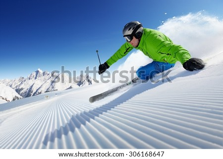 Skier on piste in high mountains with beautiful clear weather and prepared piste
