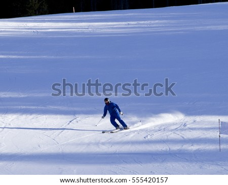 Skiers going down the slope at Aprica ski route in Italy