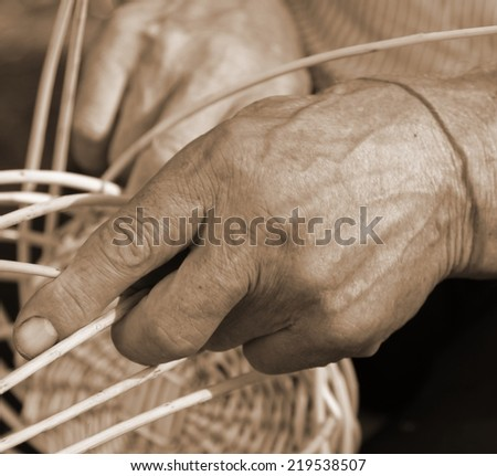 skilled craftsman who works the cane to create a big wicker basket