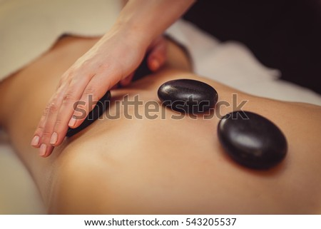 Skillful beautician undergoing massage for woman
