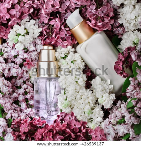 Skincare products - cream and serum - set with fresh lilac, closeup shot, lilac as background. Skincare and beauty concept.