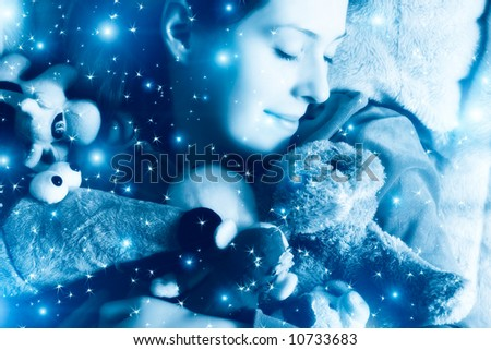 Sleeping girl with her toys. Blue tint and small fairy stars.