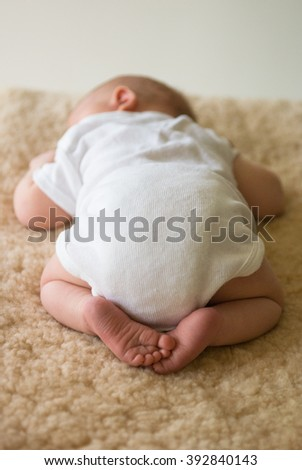 Sleeping newborn baby lying on tummy on sheepskin rug