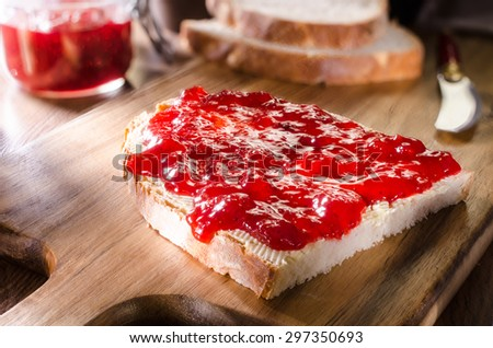 slice of bread with butter and strawberry jam on a wooden board