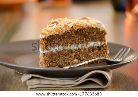 Slice of carrot cake with cheese cream frosting and almonds flakes