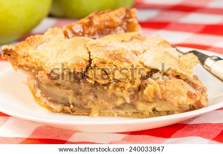 Slice of homemade apple pie on red plaid tablecloth with green apples in background.