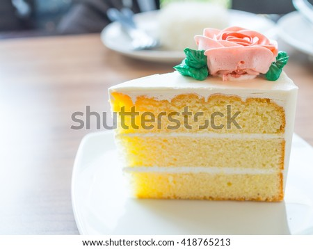 Slice vanilla cake with rose butter cream icing in the plate on wooden table background.