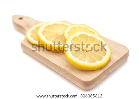 Sliced juicy lemon on small cutting board isolated